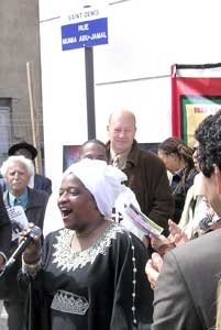 Maggy Louis sings after St. Denis<br> Mayor Didier Paillard, rear, removed<br> French flag to unveil the new<br> Mumia Abu-Jamal street sign.
