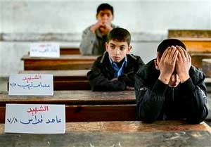 Palestinian boy Mohammed kutkut, 14, right, covers his face as he sits next to the name sign of his killed friend Ahed Qaddas in the Fakhoura boys school in Jebaliya, northern Gaza strip, Jan. 24. Three friends in his class were killed when the Israeli army shelled Jebaliya in the past weeks