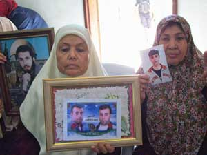 Mothers in Gaza show pictures of their<br>imprisoned sons.