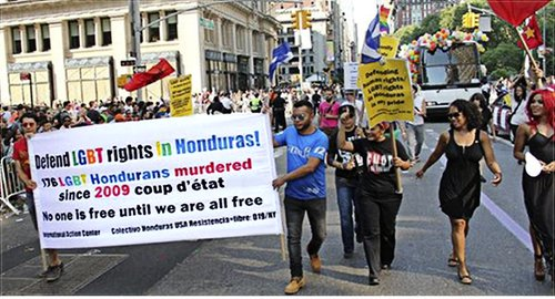 Nelson Arambú, center, carrying the banner. LeiLani Dowell, right side.PHOTO: COLECTIVO HONDURAS USA RESISTENCIA