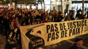 French youth protest police brutality. The banner says, 'No justice, no peace!'