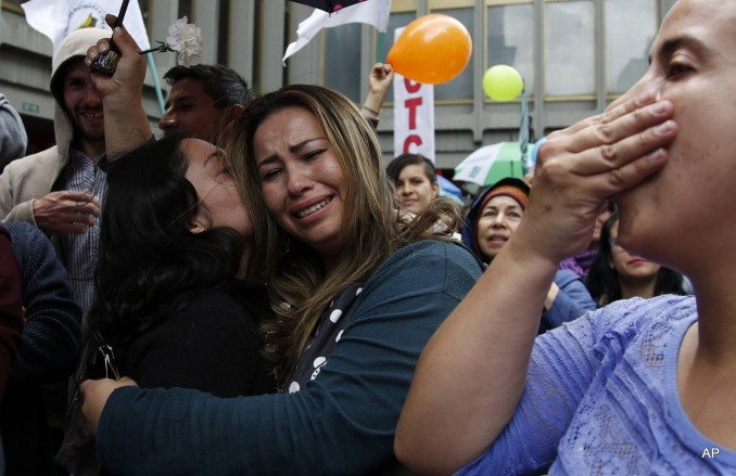 People celebrate the agreement between Revolutionary Armed Forces of Colombia, FARC, and Colombia's government, in Bogota, Colombia, Thursday, June 23, 2016.