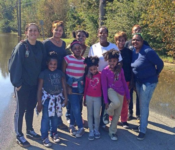 Members of the Solidarity caravan with Carolyn Dawson and Pastor Nancy Wade and Pastor Wade's family at the edge of floodwaters in East Kinston, N.C. Ms. Dawson's home is just beyond the trees.