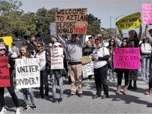 "Burlingame, Calif.  Anti-Trump protesters organized to block Republican presidential candidate Donald Trump and his supporters from basking in the California sun on April 29. Led by the Black Out Collective, Anti Police-Terror Project Bay Area, Black Lives Matter Bay Area and Black Youth Project 100, they came out to the Hyatt Regency San Francisco Airport Hotel where Trump was scheduled to give the opening address to the California Republican National Convention at noon.  Several hundred protesters succeeded in not only delaying Trump's speech at the convention by at least an hour, but forcing Trump to cross the 101 Freeway on foot and make his way through a convoluted path. The racist bigot had to squeeze between concrete barricades and walk unceremoniously through a short field, having to hop over unlevel ground, all of which was captured on camera and video. The protesters, using a variety of tactics, locked themselves down across the main access road to the hotel and pushed past police barricades up to the hotel entrance. Some even sneaked inside, where they did a spectacular banner-drop -- a bright yellow banner reading ""Stop Hate"" covered the hotel's front tower.  ""Hate has no place in the democratic process,"" said Cat Brooks, from the Anti Police-Terror Project. ""Black communities and all communities of color deserve a democracy that respects our vote, our vision and our values, not one that denies our dignity and betrays our basic humanity."" ""The RNC is spreading and encouraging a culture of hate and racism,"" said Robbie Clark, an organizer with Black Lives Matter Bay Area. ""Donald Trump represents the vile underbelly of [U.S.] democracy where Black people are both disenfranchised and disregarded. People drive the democratic process, not corporations. Black people deserve a democracy that serves us."" ""We're sending Trump packing, along with his anti-Black, anti-migrant and anti-Muslim politics. California will not be Trumped!"" said Wazi Davis, of the Black Youth Project 100. There was a large turnout from the Latino/a community, particularly local high school students. Some of them carried Mexican flags in response to Trump's racist, anti-immigrant platform and declarations that as president he would build a huge wall along the California/Mexico border. The stated goals of the protest were to reject Trump's political visit to Northern California; pressure Silicon Valley tech companies to divest funding from a Trump-led Republican National Convention; increase the visibility of Black voices and other voices of color in opposition to Trump; and demand a radical transformation of U.S. democracy where Black people have the social, economic, cultural and political power needed to thrive. Protests have sparked across the state, as the June 7 primary election approaches and Trump continues to hold rallies to build support. Five people were arrested at the Burlingame protest.  WW photo: Terri Kay"