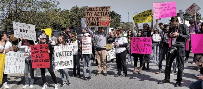 """Burlingame, Calif. Anti-Trump protesters organized to block Republican presidential candidate Donald Trump and his supporters from basking in the California sun on April 29. Led by the Black Out Collective, Anti Police-Terror Project Bay Area, Black Lives Matter Bay Area and Black Youth Project 100, they came out to the Hyatt Regency San Francisco Airport Hotel where Trump was scheduled to give the opening address to the California Republican National Convention at noon. Several hundred protesters succeeded in not only delaying Trump's speech at the convention by at least an hour, but forcing Trump to cross the 101 Freeway on foot and make his way through a convoluted path. The racist bigot had to squeeze between concrete barricades and walk unceremoniously through a short field, having to hop over unlevel ground, all of which was captured on camera and video. The protesters, using a variety of tactics, locked themselves down across the main access road to the hotel and pushed past police barricades up to the hotel entrance. Some even sneaked inside, where they did a spectacular banner-drop -- a bright yellow banner reading """"Stop Hate"""" covered the hotel's front tower. """"Hate has no place in the democratic process,"""" said Cat Brooks, from the Anti Police-Terror Project. """"Black communities and all communities of color deserve a democracy that respects our vote, our vision and our values, not one that denies our dignity and betrays our basic humanity."""" """"The RNC is spreading and encouraging a culture of hate and racism,"""" said Robbie Clark, an organizer with Black Lives Matter Bay Area. """"Donald Trump represents the vile underbelly of [U.S.] democracy where Black people are both disenfranchised and disregarded. People drive the democratic process, not corporations. Black people deserve a democracy that serves us."""" """"We're sending Trump packing, along with his anti-Black, anti-migrant and anti-Muslim politics. California will not be Trumped!"""" said Wazi Davis, of the Black You"""