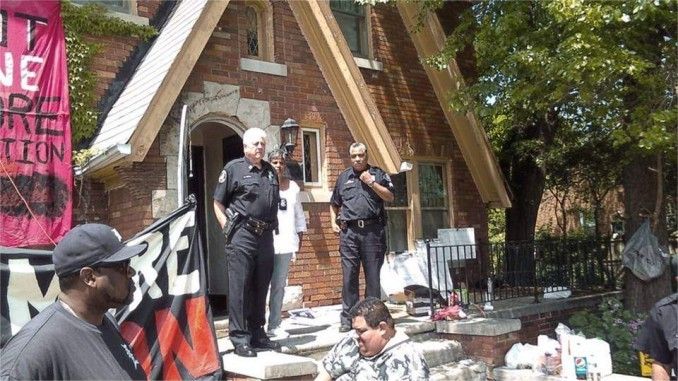 High-ranking Detroit police stand guard over the eviction of Jeanette Shannon. The bailiff is standing between the two uniformed officers.