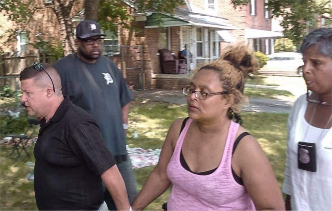 UAW Local 600 second Vice-President A.J. Freer escorts Jeanette Shannon into her besieged home to retrieve belongings. Bailiff seen wearing badge following behind.