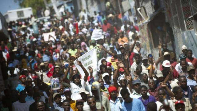 Demonstrators march against the government of Haitian President Michel Martelly.