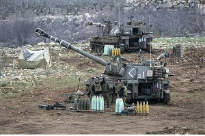 Israeli soldiers stand next to a mobile artillery unit near the border with Syria in the Golan Heights.