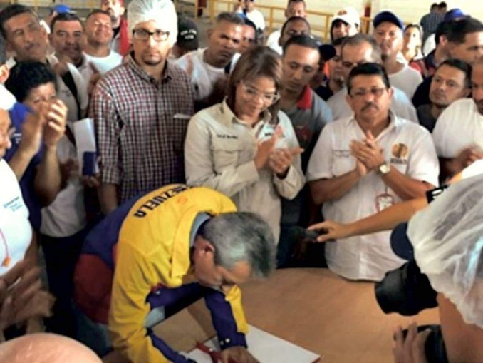 Labor Minister Oswaldo Vera signs a workers' petition to reopen the factory under worker control.